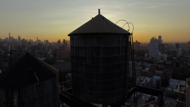 slow glide down behind water towers in soho, new york city at sunrise - tilt stock videos & royalty-free footage