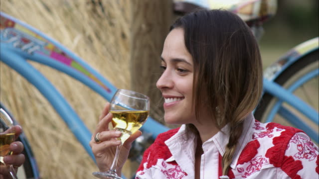 slow handheld close-up shot of a young woman enjoying white wine at an outdoor picnic - 白ワイン点の映像素材/bロール