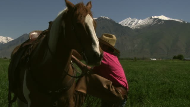 slow handheld shot of a cowboy getting on his horse - sattel stock-videos und b-roll-filmmaterial