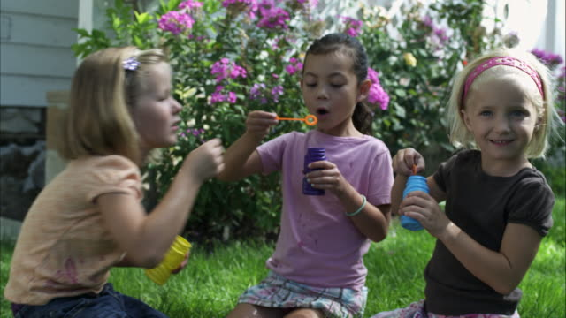 slow handheld shot of three young girls blowing bubbles in a garden - hair accessory stock videos & royalty-free footage