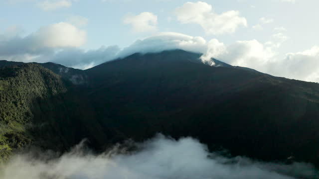 slow high elevation aerial in wispy clouds streaming by dark lush hills on sunny day - banos, ecuador - wispy stock videos & royalty-free footage