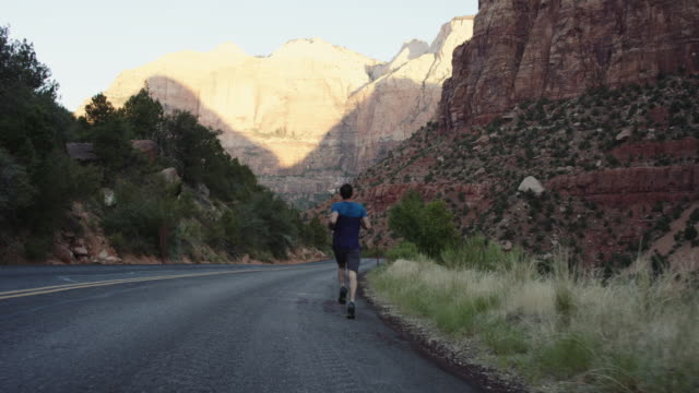 4k slow mo: athletic man jogging through zion - zion national park stock videos & royalty-free footage