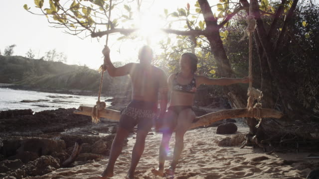 4K Slow Mo: Attractive Hawaiian Couple Sharing a Rope Swing Next to the Beach