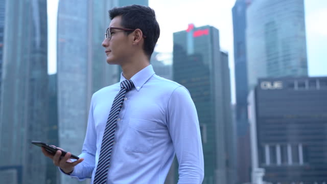 stockvideo's en b-roll-footage met ms ts slow mo businessman texting on the phone in the city. - image