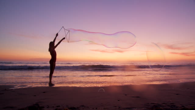 slow mo cute girl making a large bubble at sunset - bubble wand stock videos & royalty-free footage