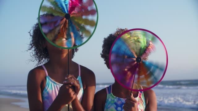 slow mo cute girls playing with pinwheels. - swimwear stock videos & royalty-free footage