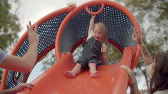 stockvideo's en b-roll-footage met slow mo cute toddler with down syndrome sliding down a slide - glijbaan speeltuintoestellen