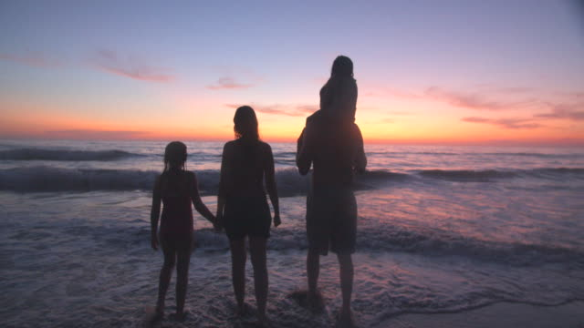 slow mo family playing on the beach at sunset - father stock videos & royalty-free footage