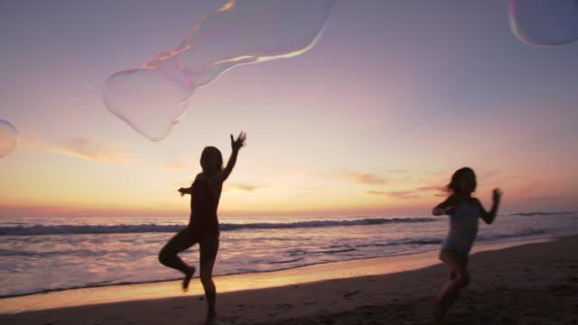 vídeos y material grabado en eventos de stock de slow mo family playing with giant bubbles on the beach - soplar