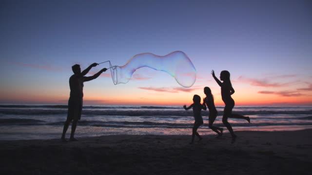 slow mo father making giant bubbles for his children - stor bildbanksvideor och videomaterial från bakom kulisserna
