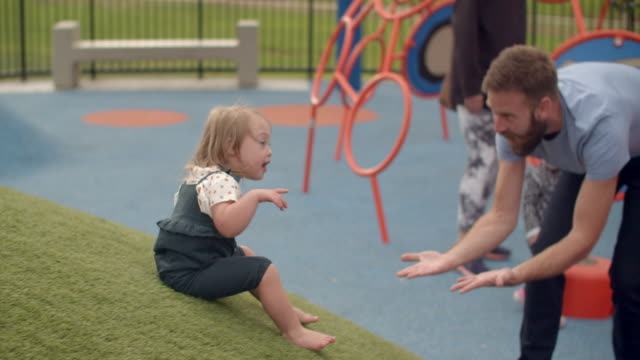 vídeos de stock, filmes e b-roll de slow mo father playing with his daughter with down syndrome at the park - parque infantil