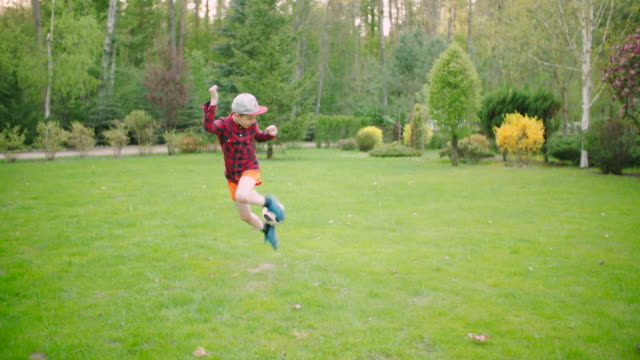 slow mo: kid and football trick - stunt stock videos & royalty-free footage