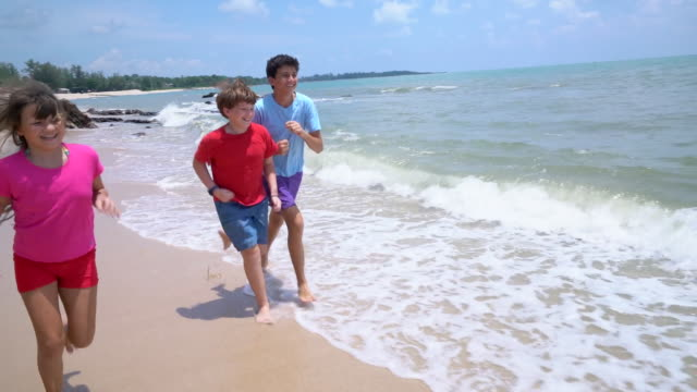 ws slow mo kids running down the beach - shorts stock videos & royalty-free footage