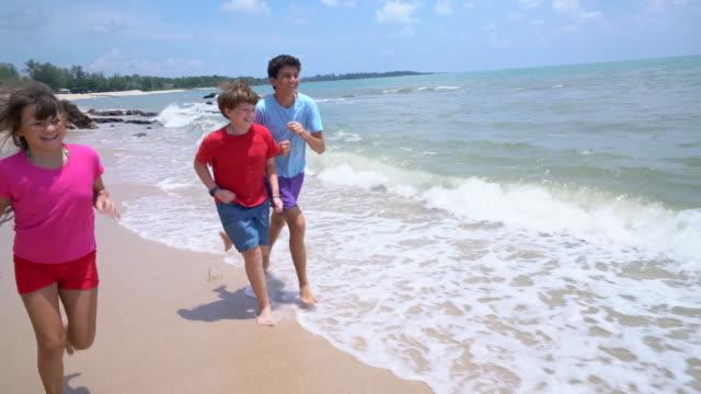 WS slow mo Kids running down the beach