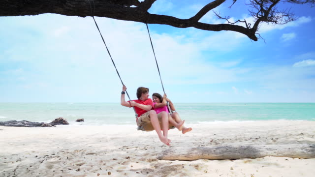 vídeos de stock e filmes b-roll de ws slow mo kids swinging on a swing by the sea. - descalço