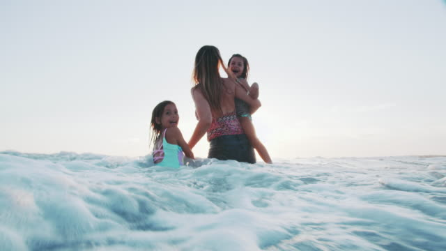 slow mo mother and daughters playing in the water - jumping stock videos & royalty-free footage