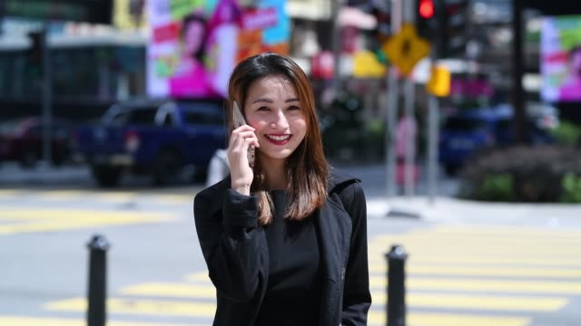 slow mo of an asian chinese female business lady talking over mobile phone , smiling and looking at the camera