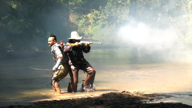 川のカウボーイと一緒に戦う古代の戦士のスローモー - 銃点の映像素材/bロール