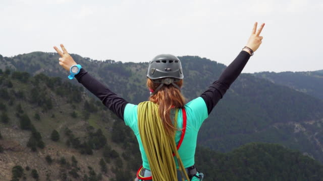 slow mo of female mountain alpine rock climber is making peace sign in the peak of a mountain - climbing equipment stock videos & royalty-free footage