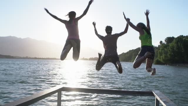 stockvideo's en b-roll-footage met slow mo rv friends jumping into a lake - steiger pier