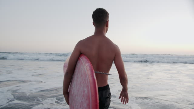 slow mo rv young man walking into the ocean with a surfboard - swimming trunks stock videos & royalty-free footage