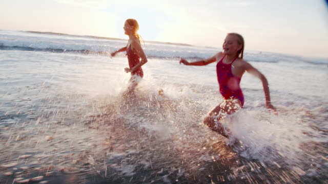 slow mo sisters playing on the beach - sunny stock videos & royalty-free footage