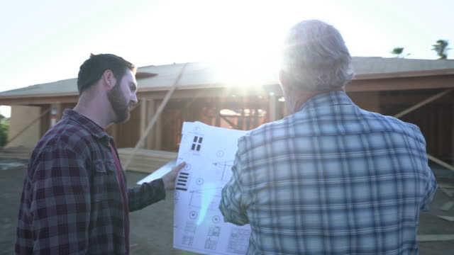 Slow Mo MS TS two men looking at plans in front of a building