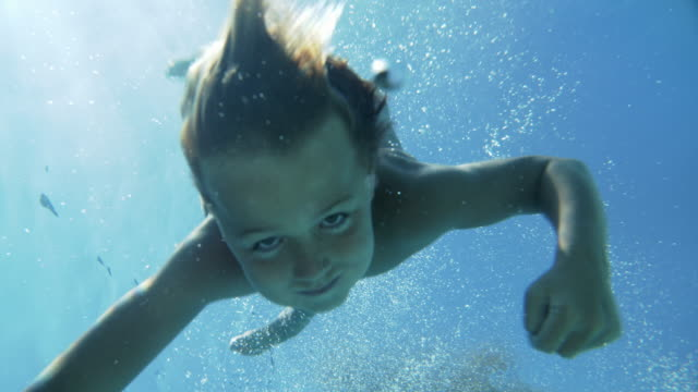slow mo young boy doing a cannonball into a swimming pool - jumping stock videos & royalty-free footage