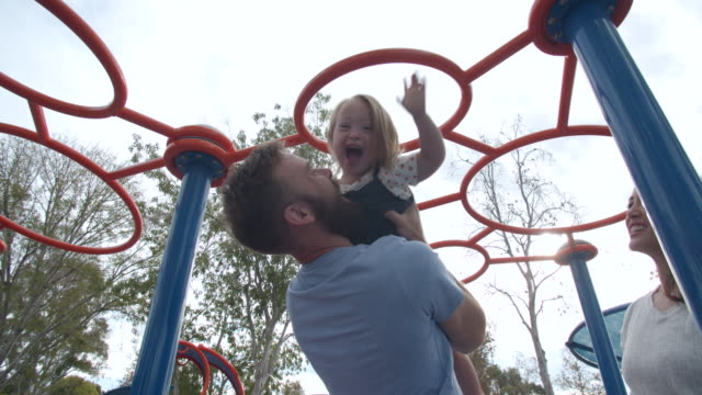vídeos de stock, filmes e b-roll de slow mo young family with down syndrome daughter playing on a jungle gym - jungle gym