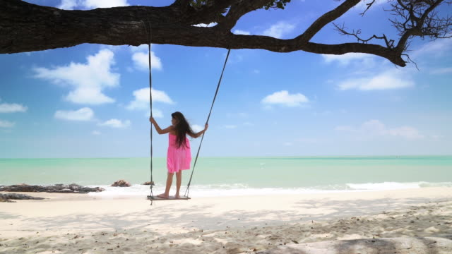 WS slow mo young girl swinging on a swing.
