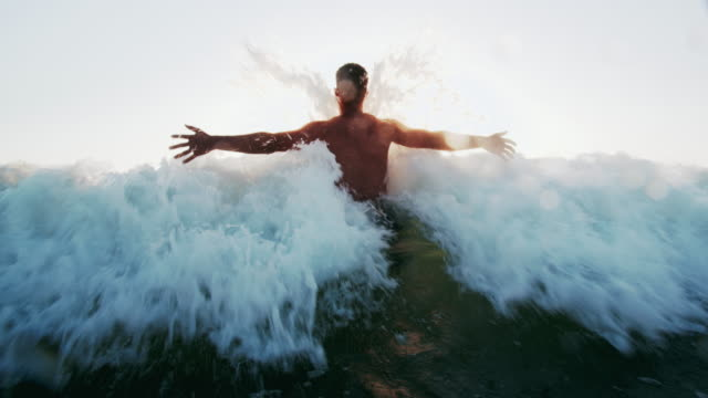 slow mo young man playing in the waves - semi dress stock videos & royalty-free footage