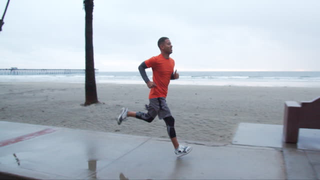 slow mo young man running in the rain - running stock videos & royalty-free footage