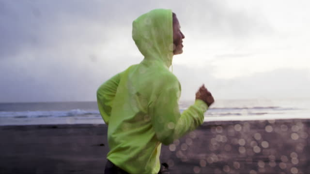 slow mo young man running in the rain - rennen stock-videos und b-roll-filmmaterial