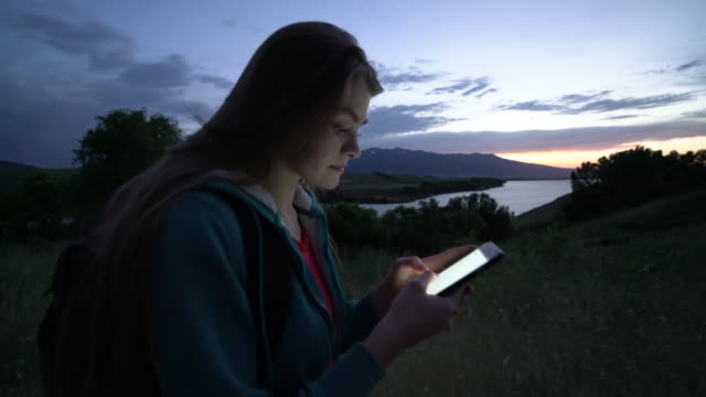 Slow Mo, MS Young woman hiking by a lake using her phone at dusk