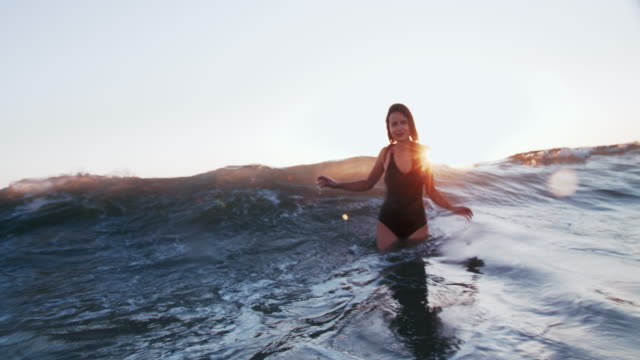 slow mo young woman playing in the waves - swimming costume stock videos & royalty-free footage