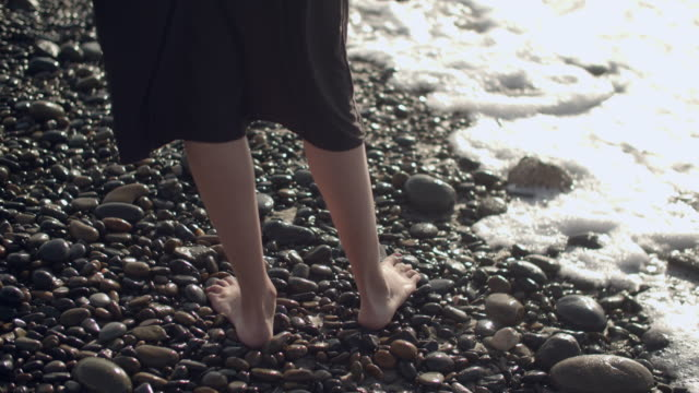 slow mo cu young woman standing on a rocky beach - barefoot stock videos & royalty-free footage
