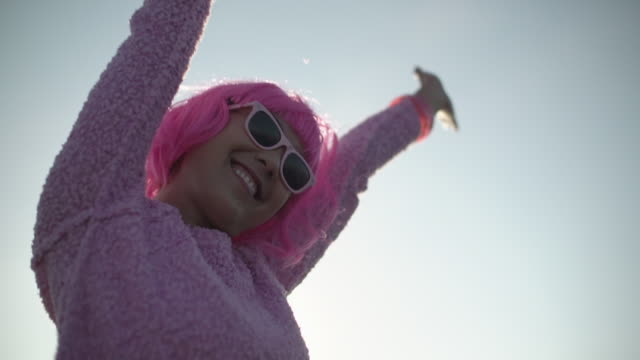 Slow Mo MS Young woman with pink hair waving her arms in the air.