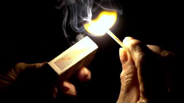 Slow mot: Closeup of hands lighting a match