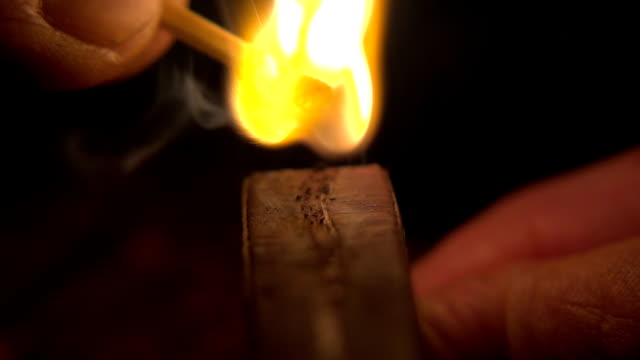 Slow mot: Closeup of hands lighting a match