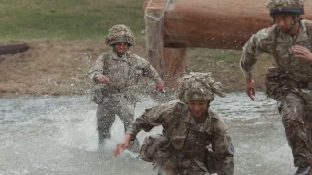 slow motion 1080p stock footage of nepalese gurkha soldiers of the british army running through water on an obstacle course - hindernisparcours stock-videos und b-roll-filmmaterial