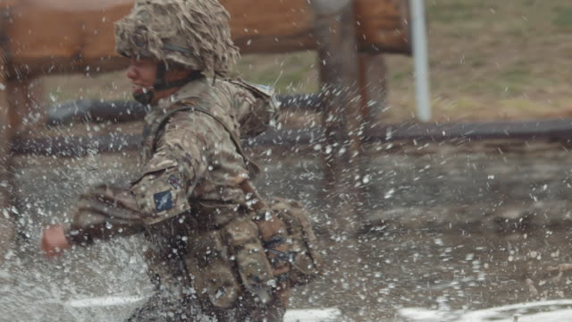 slow motion 1080p stock footage of nepalese gurkha soldiers of the british army running through water on an obstacle course - infantry stock videos & royalty-free footage