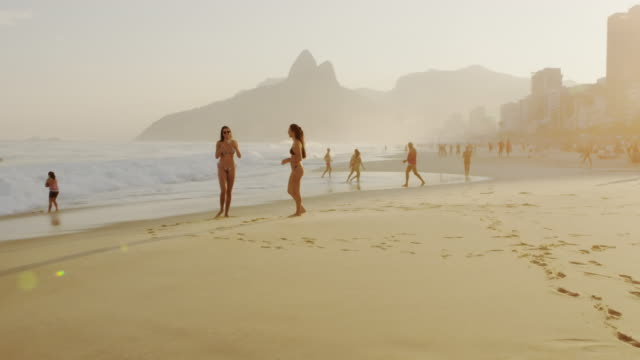 1f8726d5d7 Slow motion, 180 tracking shot of two young women in bikinis on Ipanema  beach