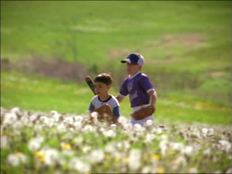 slow motion pan 2 boys in little league uniforms + baseball gloves running thru field of dandelions - youth baseball and softball league stock videos and b-roll footage