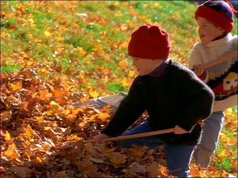 vídeos de stock e filmes b-roll de slow motion 2 boys playing in autumn leaves with rakes - ancinho equipamento de jardinagem