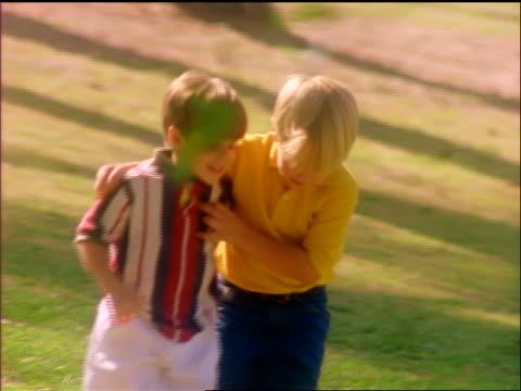 slow motion pan 2 boys (1 blonde) walking with arms around each other in park - nur jungen stock-videos und b-roll-filmmaterial
