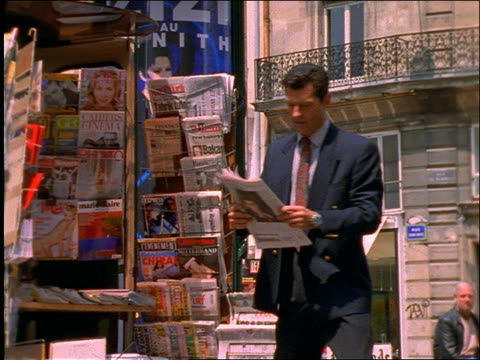 vidéos et rushes de slow motion 2 businessmen buying newspapers at newsstand / paris - kiosque à journaux