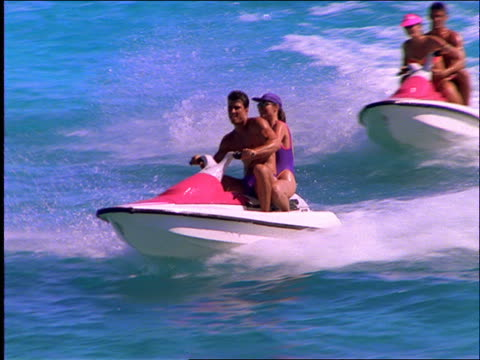 slow motion 2 couples riding jet boats on ocean / cancun - acquascooter video stock e b–roll
