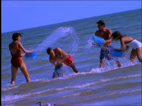 slow motion 2 couples splashing each other with pails of water / beach - swimming costume stock videos and b-roll footage
