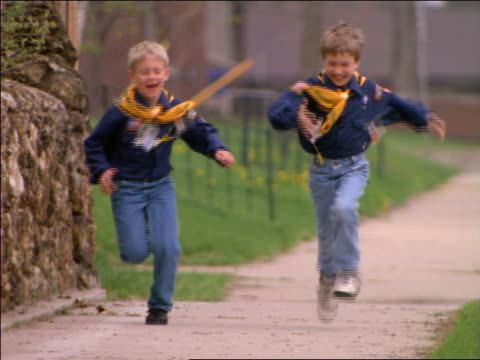 slow motion 2 cub scouts running towards camera - cub scout stock videos and b-roll footage