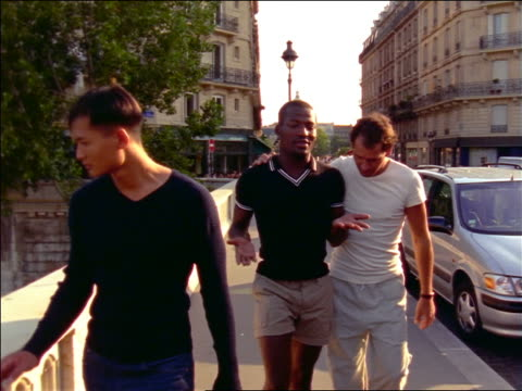 vidéos et rushes de slow motion 2 gay men (1 black) walking along seine passing gay asian man / paris, france - 1990 1999